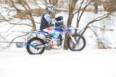 Stad Cesis, Lettland, vintermotocross, chaufför med motorcykeln och arkivbild