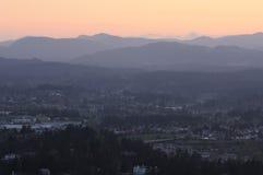 Stad en heuvels in schemer stock foto's