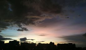 Stad för solnedgångmolnhimmel royaltyfria foton