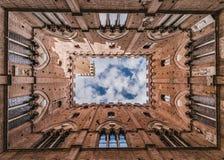 Stad Hall Bell Tower som beskådas från uteplats i Siena Arkivfoton