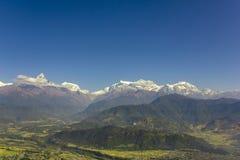 Stad i ett ljust - grön bergdal på bakgrunden av skogsbevuxna kullar och snöig maxima av Annapurna med vita moln under a royaltyfria bilder
