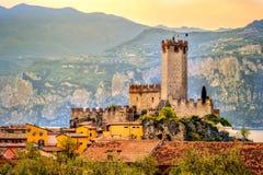 Stad och slott för italiensk bymalcesine fridsam på Garda romantisk idyllisk pittoresk solnedgång för sjöstrand royaltyfria foton
