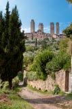 Stad och utsidaväggar och bana på den San Gimignano lodlinjen Royaltyfri Bild