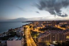Stad på banken av havet under solnedgång Royaltyfri Bild