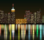 Stad på natten med reflexion i vatten Arkivbilder