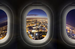 Stad på natten till och med flygplanfönster Arkivbild