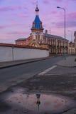 Stad på solnedgången med reflexion i en pöl Arkivfoton