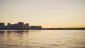 Stad p? solnedg?ngen Motorfartyg på bakgrunden av staden på solnedgången Bevattna nästan kameran stock video