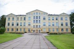 Stad Priekuli, lettisk republik Gammalt s?teri var ?r skola Gult hus och trottoar Juni 1 Foto f?r 2019 lopp arkivfoto
