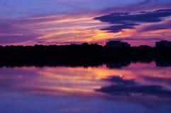 Stad sjöpanorama på solnedgången Arkivfoto