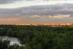 Stad under stormmolnen på solnedgången Arkivbild