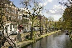 Stad van Utrecht, Nederland met kanaal, bomen, water, blauwe hemel, witte wolken en werven Stock Foto's