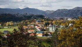 Staden av Cetinje i Montenegro omgav vid berg flyg- sikt yellow för tree för sky för blå molnig fallfältliggande ensam Royaltyfria Bilder