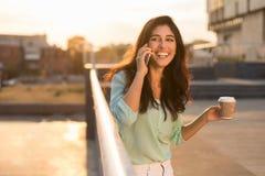 staden g?r talande kvinna f?r lycklig telefon arkivbild