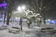 Staden parkerar på en snöig afton Arkivbild