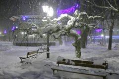 Staden parkerar på en snöig afton 1 Arkivbild