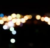 Staden tänder i bakgrunden med görande suddig fläckar av ljus Arkivbilder