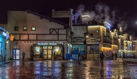 Staden tänder med nattbelysning och reflexion i pavemen Arkivfoto