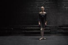 Stadigt ungt dansareanseende nära den mörka väggen arkivfoton