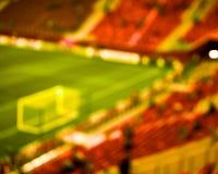 Stadio verde rosso vuoto del campo di calcio di calcio Fondo vago fuoco molle Fotografie Stock