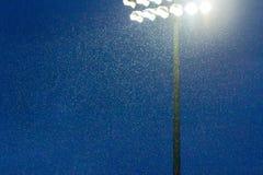 Stadionlichten die door de regen glanzen stock foto's