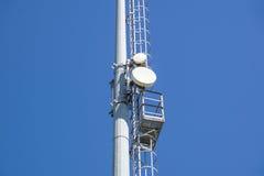 Stadionslichter und -telekommunikation im Freien ragt gegen blauen Tageshimmel hoch Stockbild