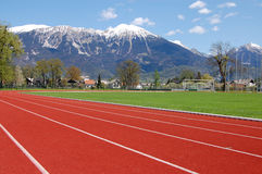Stadium. Racing track at the stadium under the snow capped mountains in spring Stock Photo