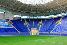 Stadium. Modern stadium with blue seats and green pay feild Royalty Free Stock Images
