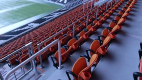 Stadium arena seats chair. Rows of orange spectator seating in a sports stadium. The empty orange or red chairs in the stands of the stadium. The stadium stock video