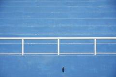 Stadium bleachers - blue. Blue stadium bleachers with white steel barriers stock photo