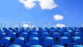 Old stadium blue benches with a blue sky in background stock photography