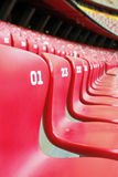 Stadium Chair. A white chair in middle of red chairs Stock Photography