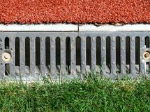 Stadium drain. With grass and artificial grass Stock Image