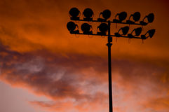 Stadium floodlights at sunset. Silhouetted stadium floodlights with sunset and cloudscape background Stock Photography