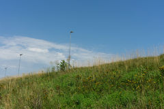 Stadium light pole with grass and sky Royalty Free Stock Images