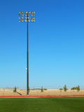 Stadium Lighting-Track and Field. Tall lights standing to illuminate a high school track and football field. Shot against a clear blue sky Royalty Free Stock Image
