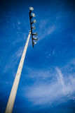 Stadium Lights. Standing against brilliant blue sky with wispy clouds Stock Photo