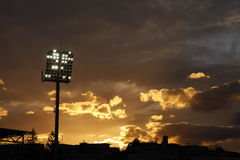 Stadium lights turned on and sunset Royalty Free Stock Photos