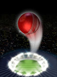 Stadium Night With Ball Swoosh. A red cricket ball swooshing into the atmosphere from a stadium with a green grass pitch under spotlights on a night city scape Royalty Free Stock Photos