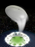 Stadium Night With Ball Swoosh. A rugby ball swooshing into the atmosphere from a stadium with a green grass pitch under spotlights on a night city scape Stock Photography