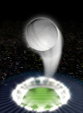 Stadium Night With Ball Swoosh. A white cricket ball swooshing into the atmosphere from a stadium with a green grass pitch under spotlights on a night city scape Royalty Free Stock Image
