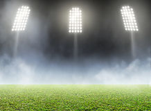 Stadium Outdoor Floodlit. A generic outdoor stadium with an unmarked green grass pitch with an eerie mist at night under illuminated floodlights royalty free stock images