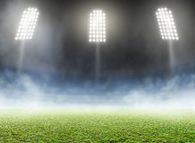 Stadium Outdoor Floodlit. A generic outdoor stadium with an unmarked green grass pitch with an eerie mist at night under illuminated floodlights - 3D render royalty free illustration