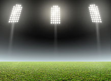 Stadium Outdoor Floodlit. A generic outdoor stadium with an unmarked green grass pitch at night under illuminated floodlights royalty free stock photography
