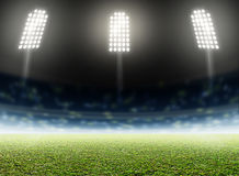 Stadium Outdoor Floodlit. A generic outdoor stadium with an unmarked green grass pitch at night under illuminated floodlights - 3D render Stock Photo