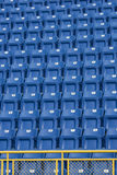 Stadium Seats. Blue seats with a yellow metal fence in front of them, at a stadium. These seats are numbered and make an ideal background stock image