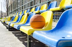 Stadium seats and basketball ball on it.Empty seats for fans at the sport court stock images