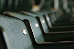 Stadium seats. Empty green stadium seats in a row with the closest clear and progressively blurring stock image