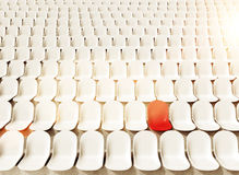 Stadium seats. Rows of white seats at stadium, one red. Toned, filter. Concept of chosen seat. 3D rendering Royalty Free Stock Images