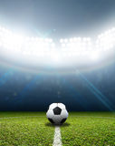Stadium And Soccer Ball. A soccer stadium with a marked green grass pitch with a soccer ball on the centre mark at night under illuminated floodlights Royalty Free Stock Image